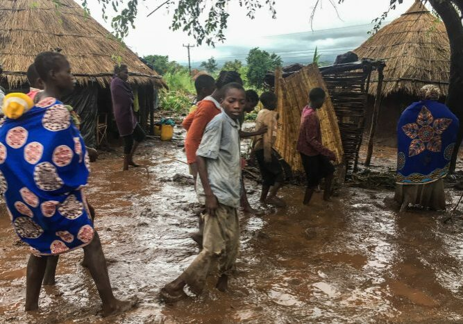 2019-03-18 16:31:49 epa07446406 Inhabitants of Chiluvi, a village in central Mozambique, walk along a flooded and muddy street after Cyclone Idai and Floods that hit the region, in Nhamatanda, Mozambique, 13 March 2019 (Issued 18 March 2019). Chiluvo, together with Nhamatanda, Sofala, illustrates the tragedy that is experienced throughout the central region of Mozambique, especially in the provinces of Sofala and Manica, where there will already be between 73 and 84 confirmed deaths, according to official figures, leaving thousands in need of relief for remaining isolated in a flooded region.  EPA/ANDRE CATUEIRA BEST QUALITY AVAILABLE