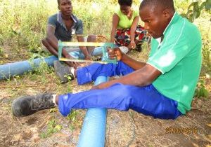 Young man using a saw to saw a pipe line